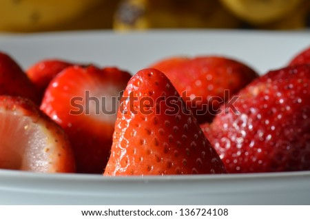 a macro shot of strawberries in a white bowl