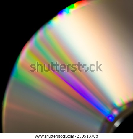 A macro shot of white light splitting into its component parts across the surface of a compact disc. - stock photo