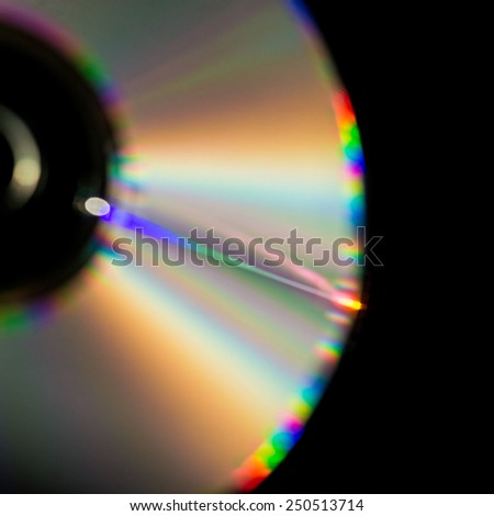 A macro shot of white light splitting into its component parts across the surface of a compact disc.