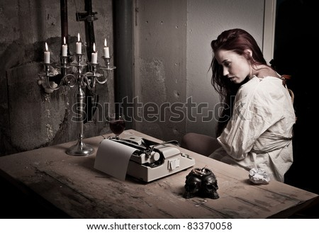 a mad girl wearing a straight jacket in front of a typewriter - stock photo