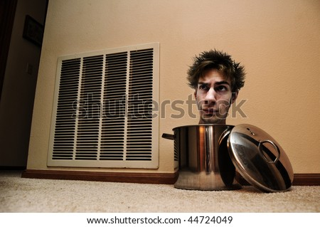 A mad man with his head peaking out of a pot laying on the floor. - stock photo