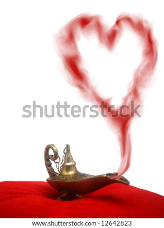A magical genie lamp with smoke on a red velvet pillow with a heart shaped smoke. - stock photo
