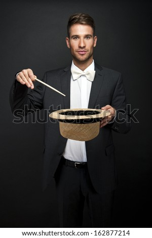 A magician in a black suit holding an empty top hat and magic wand - stock photo
