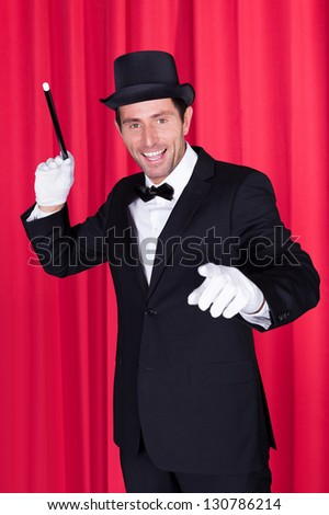A Magician In A Black Suit Holding Magic Wand - stock photo