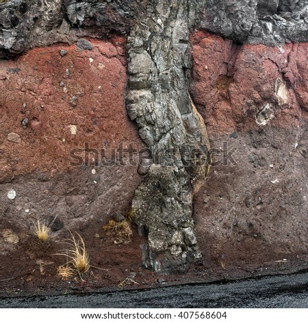A magmatic dike cross-cutting horizontal layers of rock - stock photo