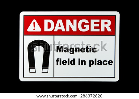 A magnetic field danger sign against a black background - stock photo