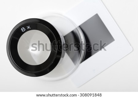 A magnification loupe sitting on a slide. Focus is on top of loupe. - stock photo