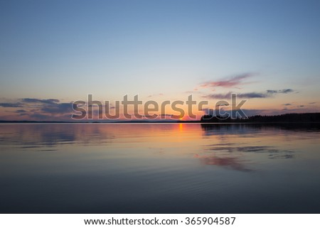 A magnificent sunset by the lake in Finland. Colorful sky reflects from the water with some clouds on the sky.