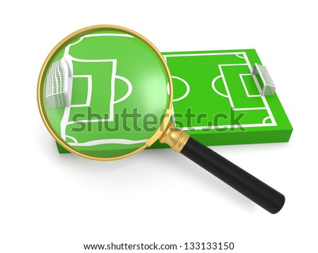 A magnifying glass, a football field model - stock photo