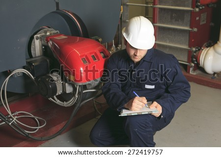 A maintenance engineer checking technical data of heating system equipment in a boiler room