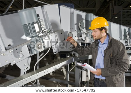 A maintenance engineer checking the status of an industrial conveyor belt, working his way down the checklist - stock photo