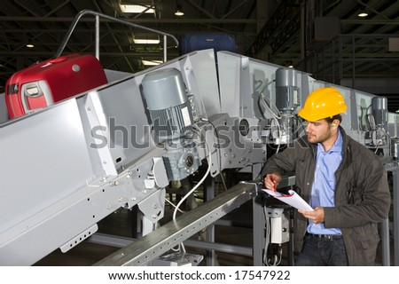 A maintenance engineer inspecting a luggage handling conveyor belt - stock photo