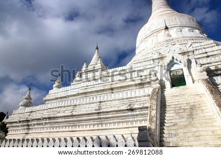 A majestic white Buddhist temple with a blue cloudy sky near the town of Mandalay, Myanmar.