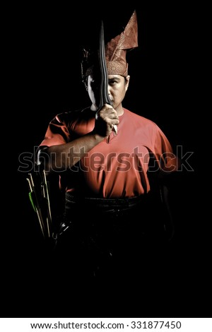 A Malay warrior with his keris in a traditional malay warrior costume isolated on black background - stock photo