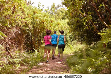 A male and his two female friends running on a jogging trail surrounded by trees in the late morning shadows wearing t-shirts and black pants