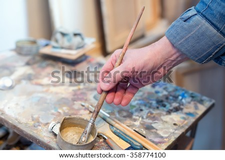 A male artist painting in his studio - stock photo