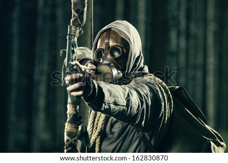 A male bow hunter wearing gas mask, draws back on his bow - stock photo