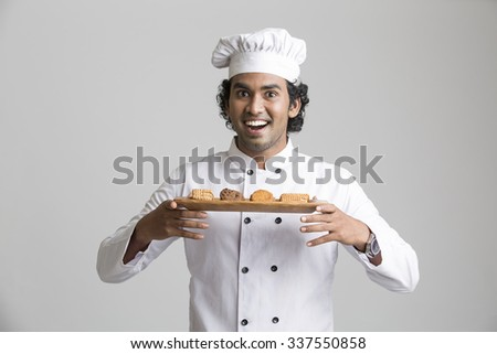 A male chef posing with cookies isolated over grey gradient background - stock photo