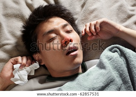 A male Chinese man is sleeping while catching cold and breathing through mouth because of the flu - stock photo
