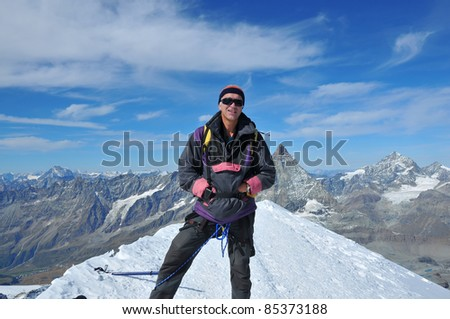 a male climber on the summit of a mountain with the Matterhorn in the background.