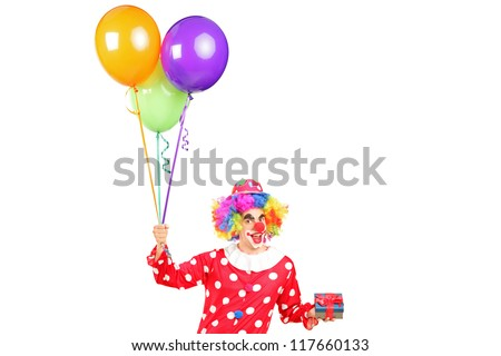A male clown, happy joyful expression on face, with a bunch of balloons and a gift isolated on white background