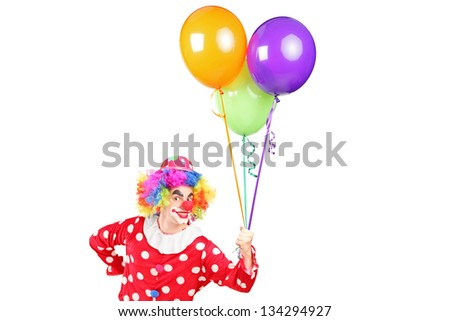 A male clown in costume holding bunch of balloons isolated on white background