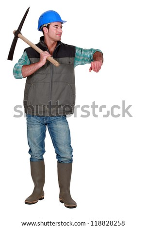 A male construction worker with a pickaxe. - stock photo