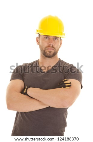 A male construction worker with a yellow hardhat and a serious expression on his face with his arms folded. - stock photo