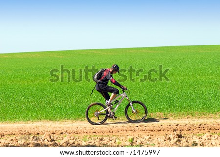 A male cyclist riding a bike over green field;  clear summer day