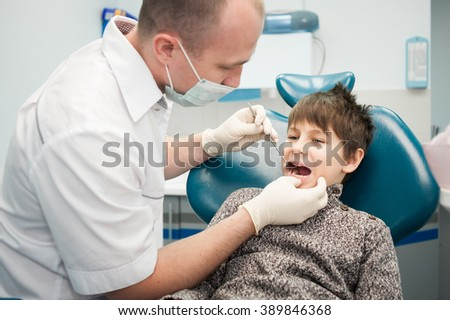 A male dentist examining a young boys teeth, dental nurse in the background