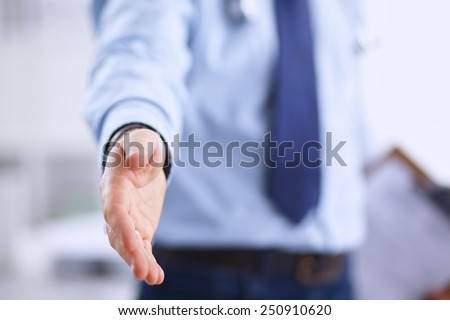 A male doctor giving his hand for a handshake - stock photo