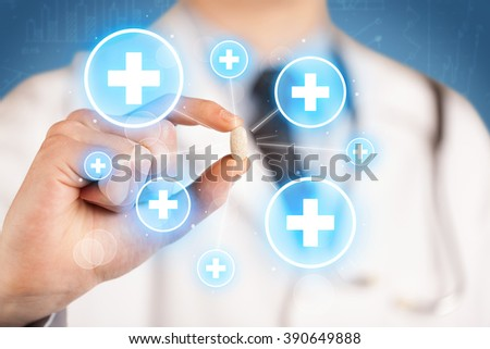 A male doctor in coat in front of a blue wall holding a pill between his fingers with lines and white crosses in circles - stock photo