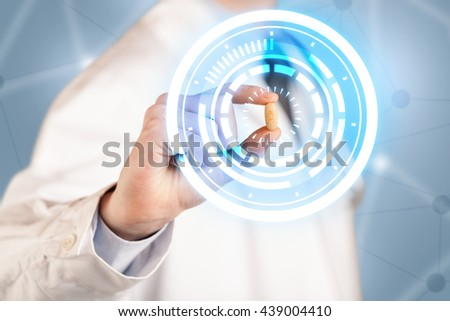 A male  doctor in white coat showing a glowing pill in blue, white circles - stock photo