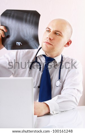 A male doctor studying a x-ray image, sitting at the desk, isolated on white background
