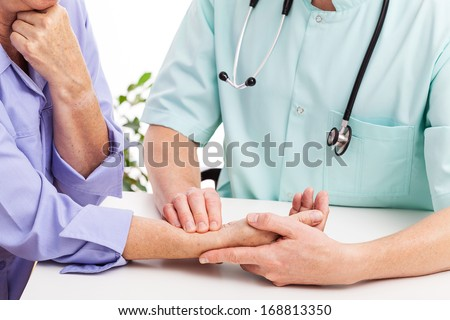 A male doctor taking his patient's pulse