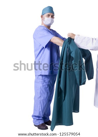 A male doctor with a face mask wearing a blue scrub suit on a white background - stock photo
