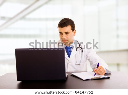 A male doctor working at the desk in hospital office