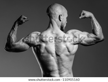 a male fitness model posing his fit body - stock photo
