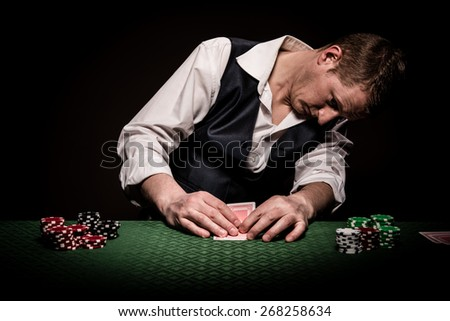 A male gambler checks once his cards on the table before placing the bet - stock photo