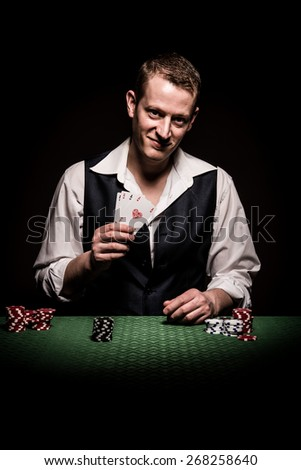 A male gambler makes four aces and winning hand - stock photo