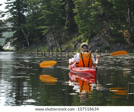 A male glides a kayak through quiet water on a peaceful wilderness lake.