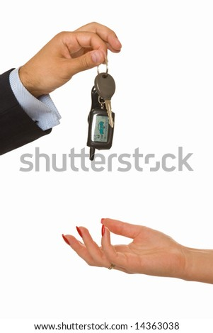 A male hand drops a bunch of car keys into a female hand
