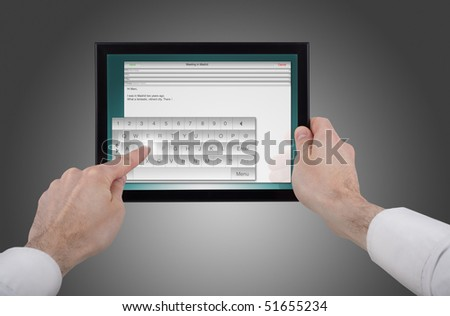a male hand holding a touchpad pc, one finger touches the screen and writes an e-mail - stock photo