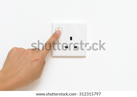 A male hand is pushing a switch on a wall socket