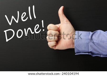 A male hand wearing a business shirt giving a thumbs up gesture for the phrase Well Done! written on a blackboard