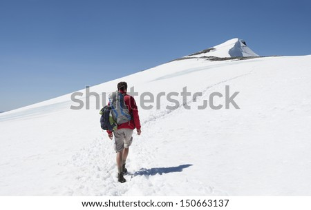 A male hiker on his way to the summit of Glittertind mountain in the snow (Jotunheimen National Park, Norway)