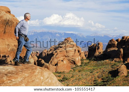 A male hiker stands on a boulder ridge overlooking a portion of the Arches National Park, Utah, USA.