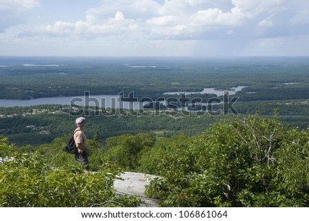 A male hiker stands on a ridge overlooking the wilderness of northern Ontario in Killarney Provincial Park. - stock photo