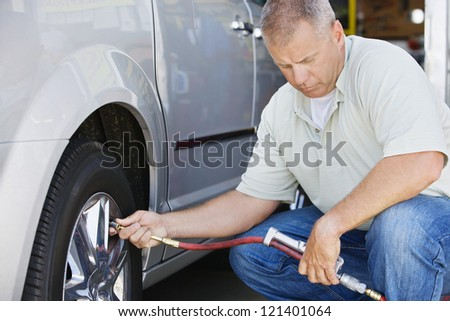 A male mechanic inflating car's tire - stock photo