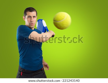 a male paddle tennis player with green background - stock photo